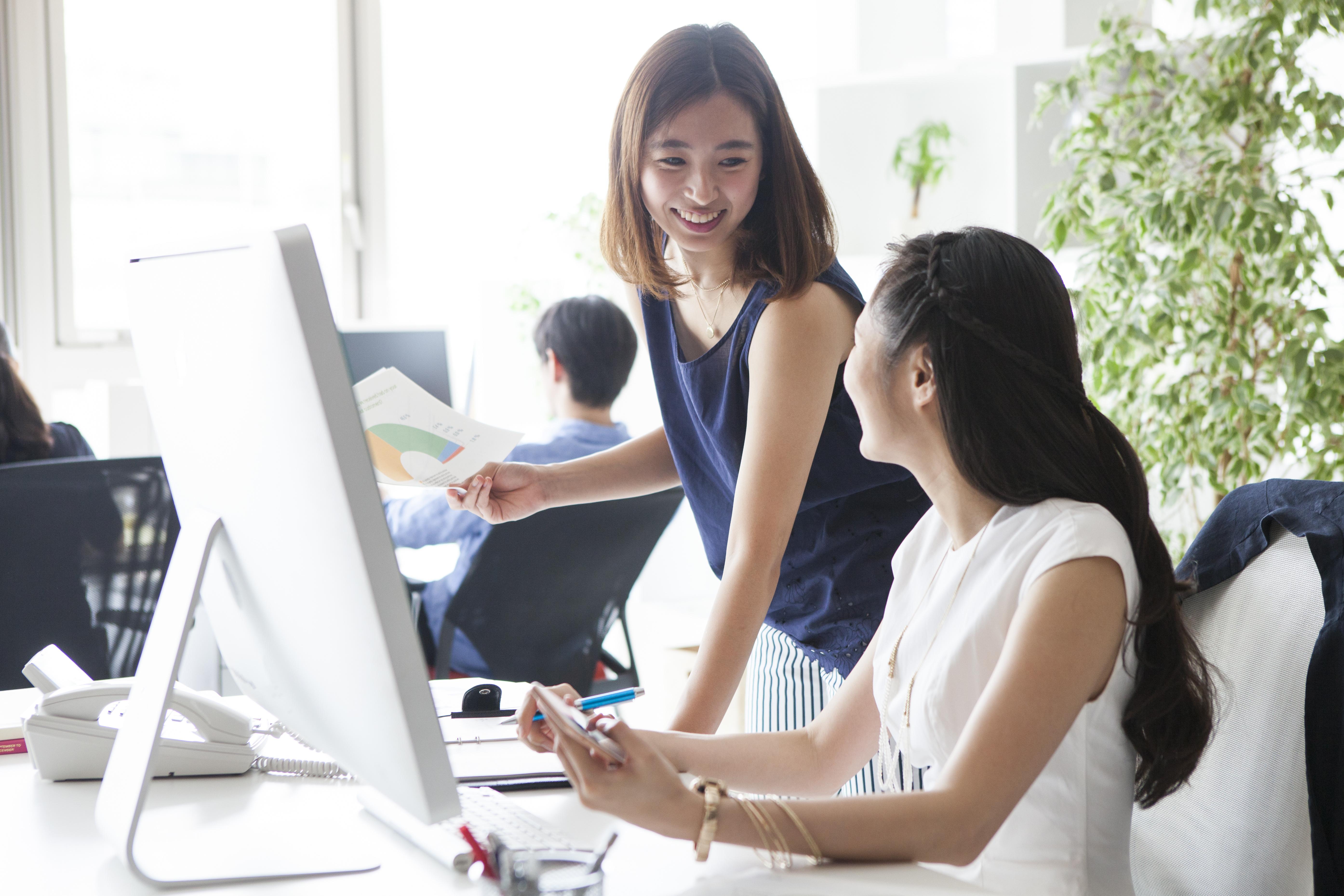 女性社員たちは楽しそうにオフィスで働いている