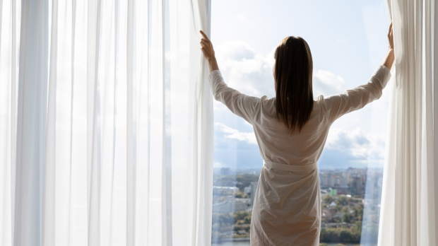 Rich young woman wear gown open curtains stand at window